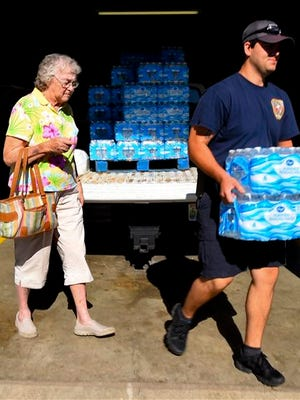 Travis Tanner of the Mud Tavern, Ala. Volunteer Fire Department carries cases of water for Shelby Randolph on June 8, 2016 in Decatur, Ala. Several shipments containing thousands of gallons of donated water from grocery stores, food banks and others arrived in Morgan and Lawrence counties over the past few days to be distributed at five locations in each county. The water is being sent after testing found chemicals in a northern Alabama water system. (John Godbey/The Decatur Daily via AP) MANDATORY CREDIT