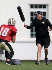 New Orleans Saints quarterback Garrett Grayson, left, and quarterback coach Pete Carmichael go through a drill during training camp at The Greenbrier in White Sulphur Springs, W.Va., Friday, Aug. 5, 2016.