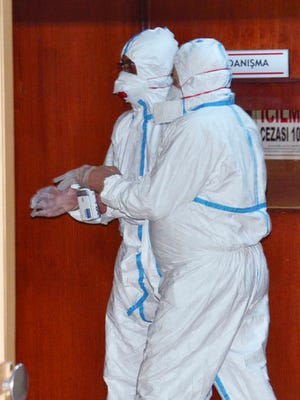 In this photo taken on late Wednesday, April 5, 2017 and made available Thursday, April 6, World Health Organization experts work as they take part in an autopsy conducted in a hospital in Adana, Turkey.  Turkey's Justice Minister Bekir Bozdag said autopsy results show Syrians were subjected to chemical weapons attack in Idlib, Syria, on Tuesday.