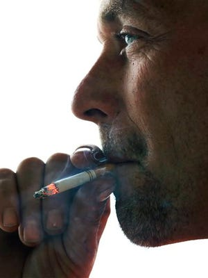 John Cormier smokes a cigarette on Main Street in Westminster, Mass., Thursday, Nov. 6, 2014. Local officials are contemplating what could be a first: a blanket ban on all forms of tobacco and e-cigarettes, leaving some shop owners fuming. (AP Photo/Elise Amendola)