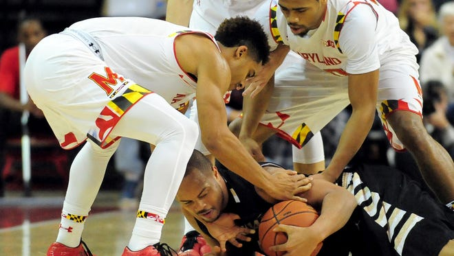 Oakland Golden Grizzlies forward Ralph Hill (0) fights for a loose ball with Maryland Terrapins guards Melo Trimble (L) and Richaud Pack (R) in the second half at Xfinity Center.