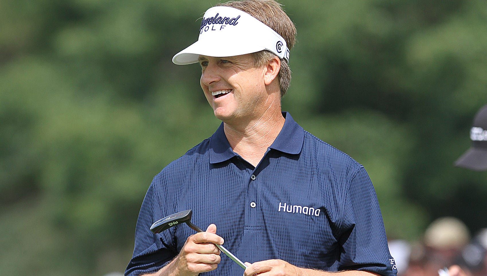 David Toms smiles after sinking a putt.