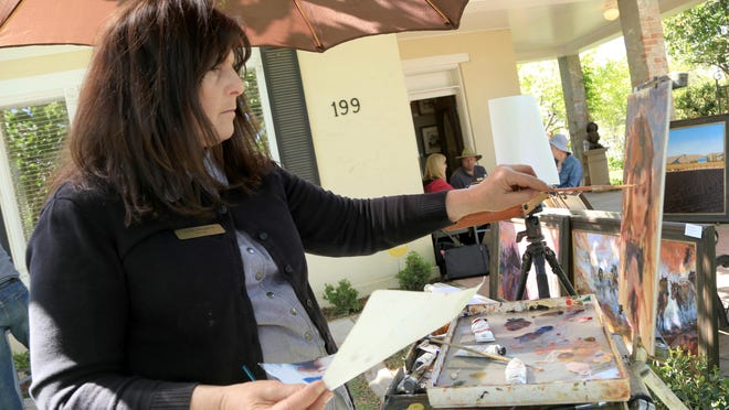 """Julie Rogers paints during the 2015 New Visions Art Show outside Authentique Gallery in St. George. The Kanab-based artist also took part in this year's """"Where In The World Is ..."""" plein air art show Wednesday through Friday."""