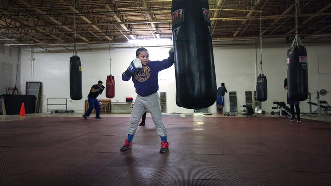Vision Lawrence, 11, of College Hill, lands a punch on the bag at Real Deal Boxing Club in Mt. Healthy, where members of Fighting Chance practice boxing and obtaining life goals Wednesday.