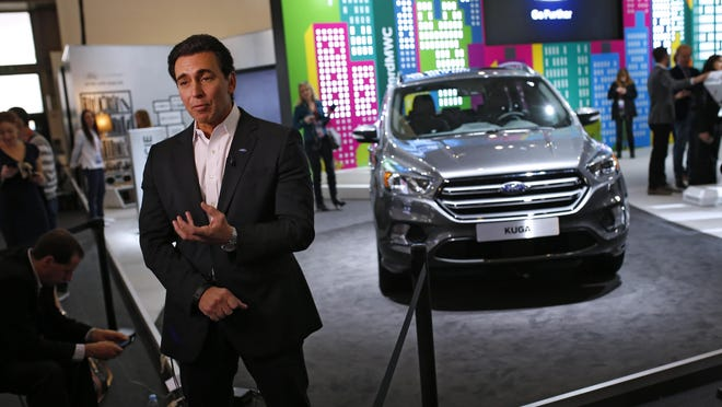 Ford CEO Mark Fields stands next to the new Kuga SUV, which features Ford's latest connectivity and driver-assisted technology.