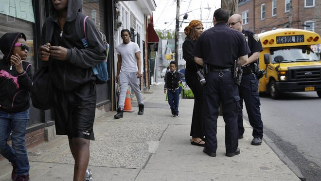 Police officers talk with community activist Cynthia Davis in the Staten Island borough of New York, Tuesday, May 24, 2016. The recent highly publicized deaths of black men in encounters with police in Minnesota, Louisiana and across the country, and now the sniper killing of five Dallas officers, have focused new attention on the chasm between police and minorities, one of so many divides in this contentious election year. Years of tension have left people wary in both the policing community and in minority neighborhoods, with many yearning for one another's respect. (AP Photo/Seth Wenig)