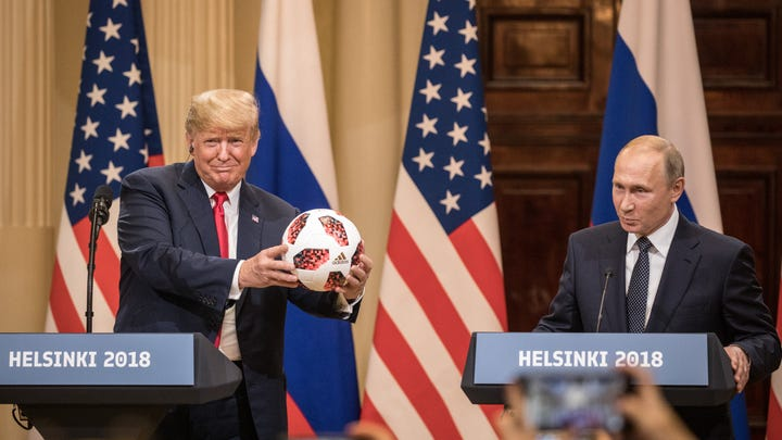 HELSINKI, FINLAND - JULY 16:  U.S. President Donald Trump (L) poses with a football given to him by Russian President Vladimir Putin during a joint press conference after their summit on July 16, 2018 in Helsinki, Finland. The two leaders met one-on-one and discussed a range of issues including the 2016 U.S Election collusion.  (Photo by Chris McGrath/Getty Images) ORG XMIT: 775193097 ORIG FILE ID: 1000198630