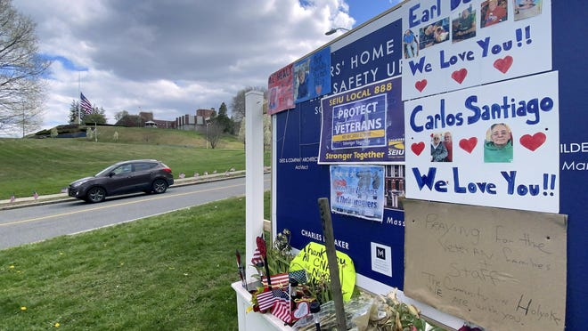 Tributes to veterans cover a sign Tuesday near an entrance road to Soldiers' Home in Holyoke, Mass., where a number of people died due to the coronavirus.