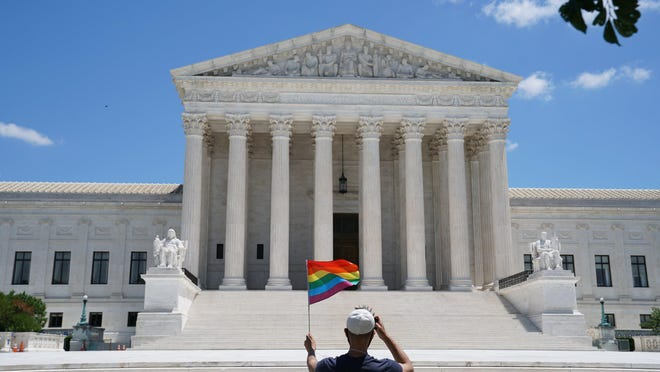 A person waves a rainbow flag in front of the Supreme Court in Washington on Monday, June 15, 2020. The Supreme Court ruled Monday that a landmark civil rights law protects gay and transgender workers from workplace discrimination, handing the movement for L.G.B.T. equality a stunning victory.