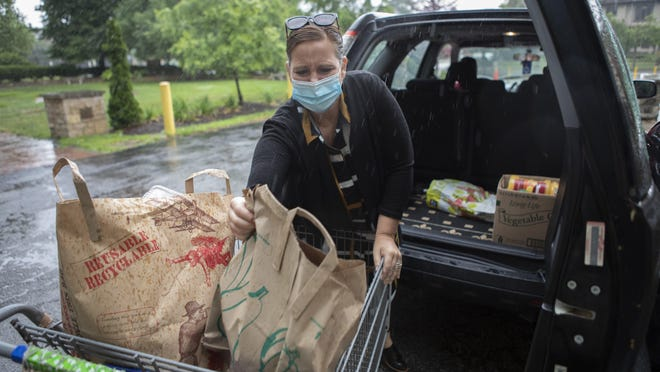 Volunteer Lydia Strauss loads groceries into the back of a car at the Broad Street Food Pantry inside Broad Street Presbyterian Church in Columbus on Tuesday.