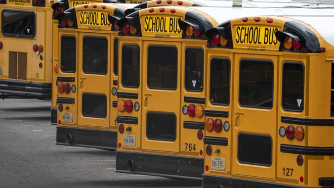 Fairfax County Public School buses are lined up at a maintenance facility in Lorton, Va., Friday, July 24, 2020. The nation's 10th largest school district plans an all-virtual start to the fall semester amid the Covid-19 pandemic.