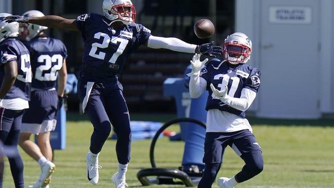 Patriots defensive backs J.C. Jackson (27) and Jonathan Jones (31) perform a drill during training camp on Sunday.