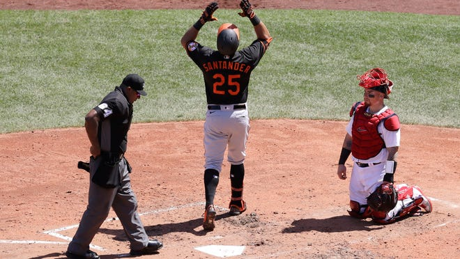 The Orioles' Anthony Santander, center, celebrates a two-run homer in the fourth inning as he arrives at the plate while Red Sox catcher Christian Vazquez, right, looks on.