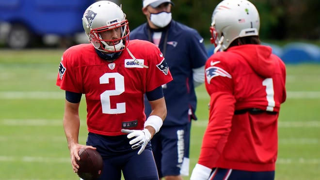 Patriots quarterbacks Brian Hoyer, left, and Cam Newton go over a drill during training camp at Gillette Stadium.