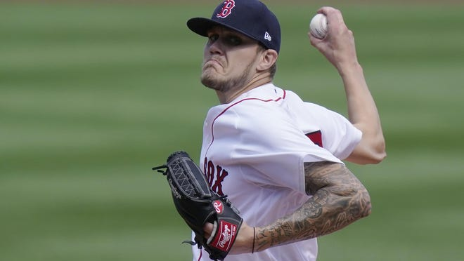 Boston Red Sox's Tanner Houck winds up for a pitch against the New York Yankees in the first inning Sunday in Boston.