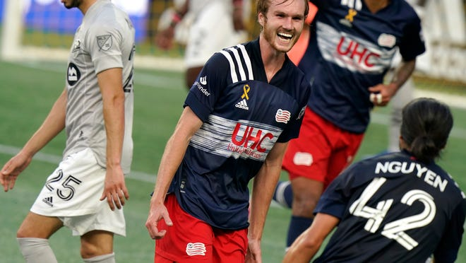 The Revolution's Henry Kessler, center, celebrates with teammate Lee Nguyen, right, after scoring in the first half against the Montreal Impact on Wednesday night in Foxboro.