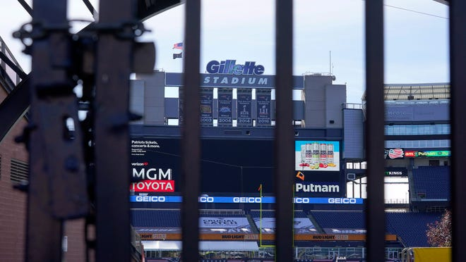 The Gillette Stadium logo stands above an empty field at the stadium that is home to the New England Patriots football team, Sunday, Oct. 11, 2020, in Foxborough, Mass. The NFL has postponed the Denver Broncos-New England Patriots game due to another positive coronavirus test with the Patriots.
