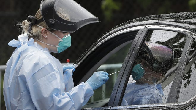 FILE - A medical worker administer a test for the coronavirus to a person in a vehicle, Thursday, June 11, 2020, in the Roxbury neighborhood of Boston.