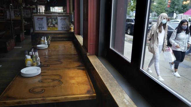 Passersby walk past an empty restaurant, left,  in Boston.