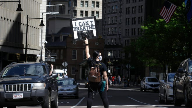 Protester Christina Aiello, of Boston, displays a placard as she stands in an intersection Sunday, May 31, 2020, in Boston as she demonstrates against the death of George Floyd who died after being restrained by Minneapolis police officers on May 25.