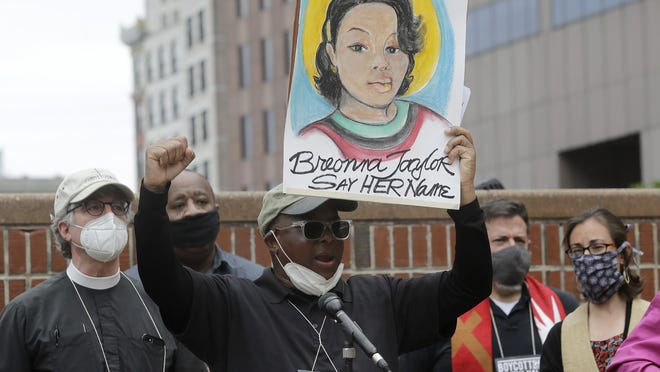 Kevin Peterson, founder and executive director of The New Democracy Coalition, center, displays a placard showing fallen Breonna Taylor as he addresses a rally on Tuesday in Boston. Petersen advocates for changing the name of Faneuil Hall, as its namesake Peter Faneuil, was a slave owner.