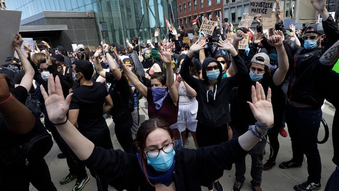Protesters demonstrate Sunday, May 31, 2020, in Boston, over the death of George Floyd who died after being restrained by Minneapolis police officers on May 25.