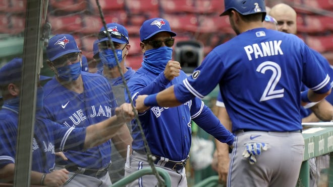 Toronto Blue Jays' Joe Panik (right) is welcomed to the dugout after scoring on a double by Cavan Biggio, not shown, in the fifth inning of a baseball game against the Boston Red Sox ib Sunday in Boston.