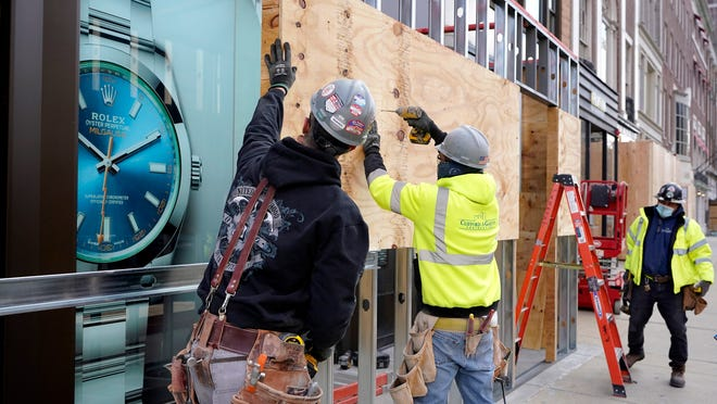 Ahead of results from the presidential election, worker Brian Buckley, of Chester, N.H., left, works with others from Clifford & Galvin Contracting, LLC, Tuesday, Nov. 3, 2020, to board up the Rolex by Long's jewelry store in the fashionable Newbury St. shopping district, in Boston.