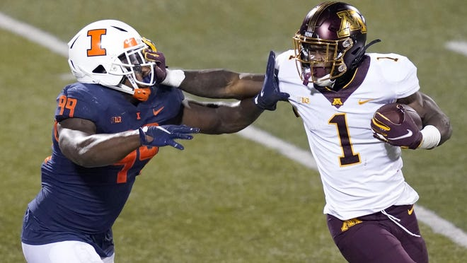 Minnesota running back Cam Wiley (1) stiff arms Illinois defensive lineman Owen Carney Jr. during the second half of an NCAA college football game Saturday, Nov. 7, 2020, in Champaign , Ill. Minnesota won 41-14.