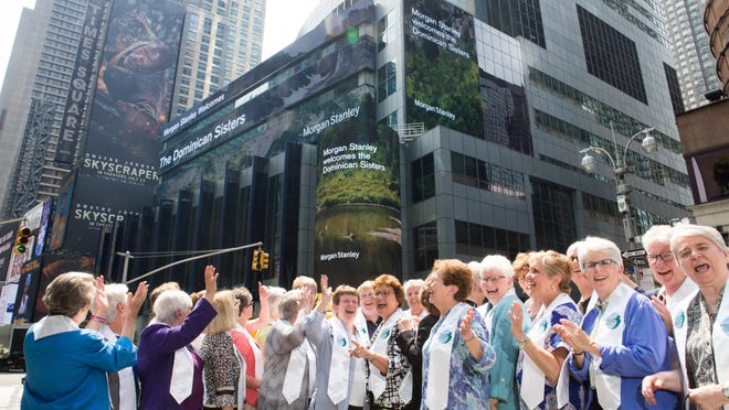 Representatives of the 16 U.S. congregations of the Dominican Sisters react to the electronic welcome from investment firm Morgan Stanley as they gather on June 18, 2018, at the firm's headquarters on Times Square, New York, to celebrate the inauguration of the Climate Solutions Funds.