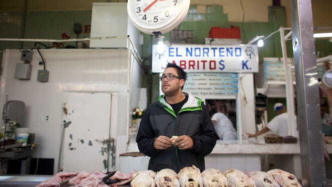 """In this July 27, 2012 file photo, U.S. chef Christopher Kostow talks to a vendor as he shops at a food market in Mexico City. Kostow, who started out studying philosophy, has a three Michelin star rating for his work at The Restaurant at Meadowood, located in a lush Napa Valley resort. """"Studying philosophy did teach me to absorb a lot of information with a critical eye and then use that information in a singular and personal manner,"""" he writes in his first book, """"A New Napa Cuisine,"""" coming out in October 2014."""