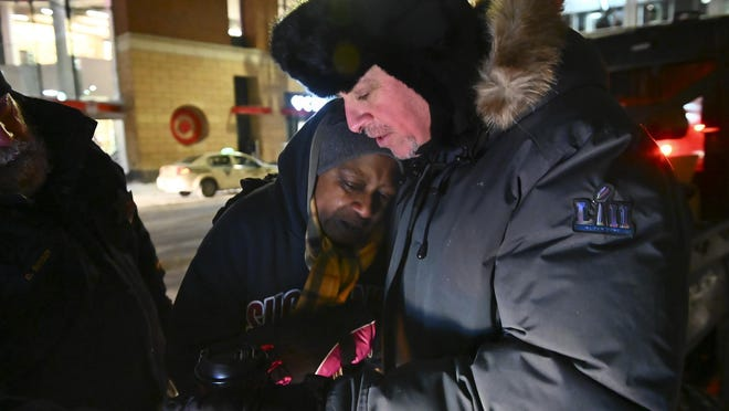 Pastor John Steger, with Grace in the City church, embraces Jearline Cyrus, a homeless woman, in downtown Minneapolis, Jan. 29, 2019, while delivering cold-weather gear, hot chocolate and food with Minneapolis Police Sgt. Grant Snyder.