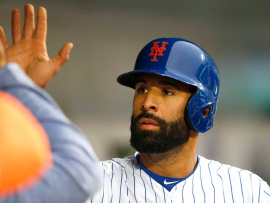 Mets left fielder Jose Bautista celebrates in the dugout