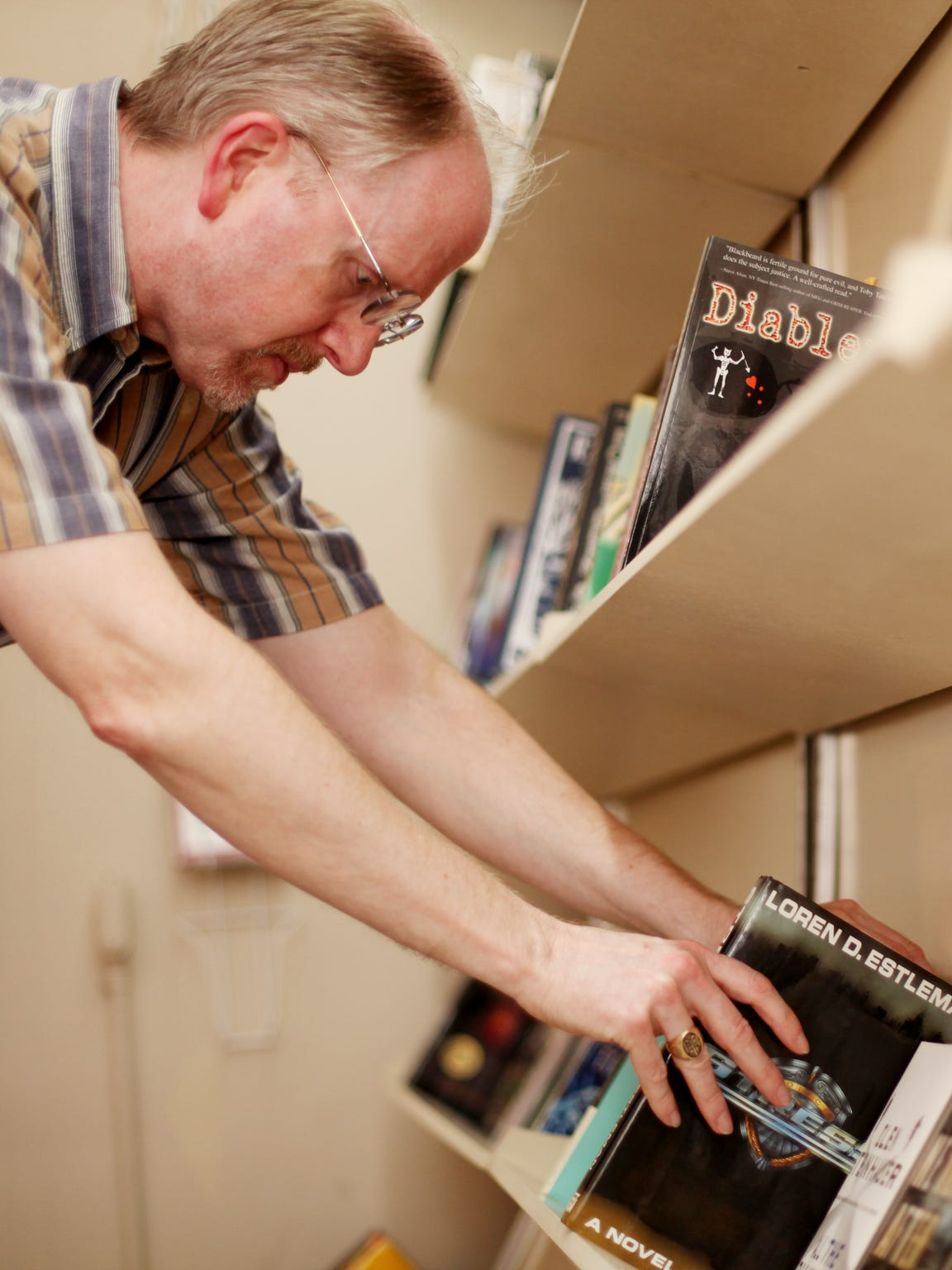Ron Ramsey, owner of Bookworks, arranges books in his