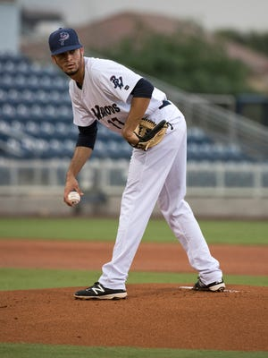 Blue Wahoos pitcher Jesus Reyes checks the runner at first before delivering his next pitch during Wednesday's games against the Biloxi Shuckers.