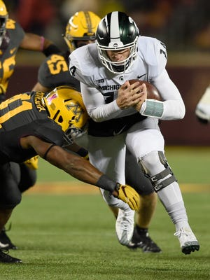 Michigan State quarterback Brian Lewerke carries the ball against Minnesota's Thomas Barber during the third quarter of MSU's 30-27 win on Saturday, Oct. 14, 2017, in Minneapolis.