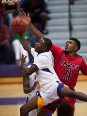 Fort Pierce Central's Devion Pierre-Louis puts a shot up against Vero Beach's Javian Cuff in the first half of their high school boys basketball game at Fort Pierce Central High School on Tuesday, Dec. 12, 2017, in Fort Pierce.