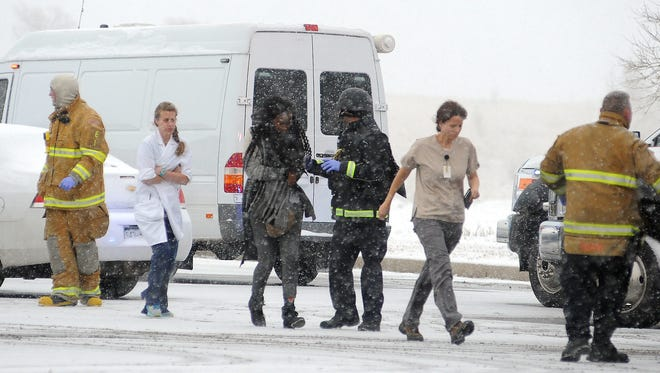 People are escorted away after a deadly shooting at a Planned Parenthood clinic on Friday in Colorado Springs, Colo.