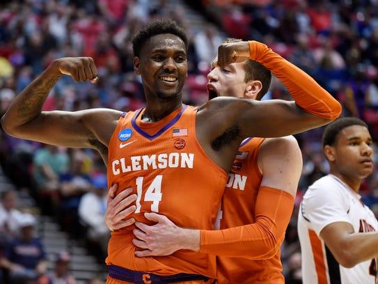 Clemson forward Elijah Thomas, front, celebrates a