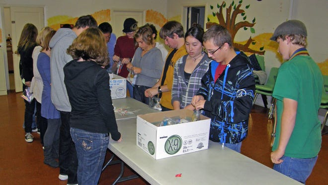 """Youngsters from the Reno First United Methodist Youth Fellowship assemble hygiene kits for guests of the """"Drop in the Bucket"""" food pantry in 2011. Christians worth their salt are to feed the hungry, clothe the naked, care for the sick, and visit those in prison, says Emerson."""