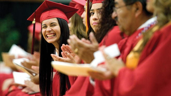 A graduate smiles during the commencement at Porterville College, in Porterville, Calif., in May 2015.