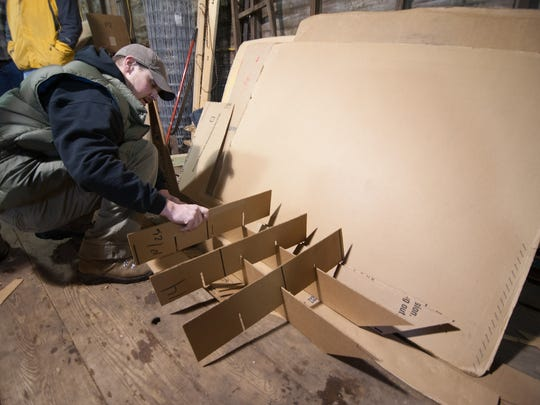 Michael Kulik places cardboard supports on his Moustache Sled. Kulik said that the supports will allow the cardboard sled to carry in excess of 600 pounds during the run down the hill.