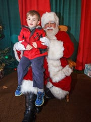 Three-year-old Connor McNeil of Stone Bank visits with Santa at The German Christmas Market in Oconomowoc.