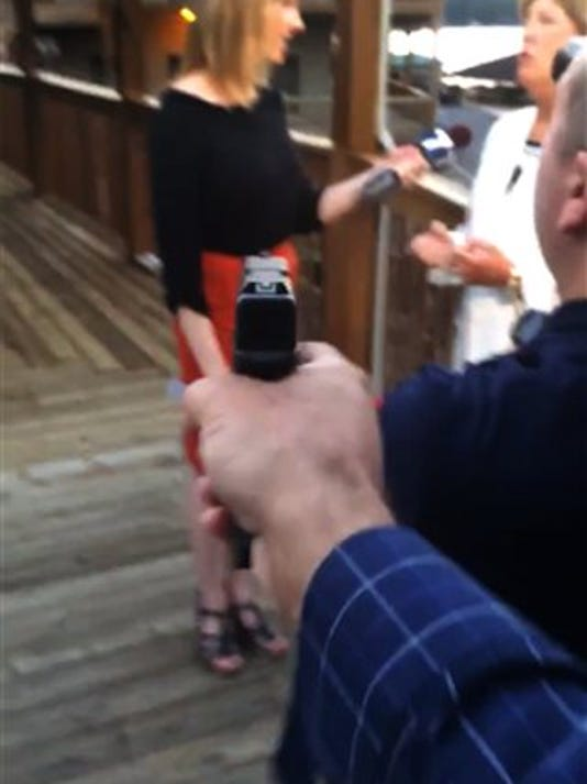 ADDS DATE - In this framegrab from video posted on Bryce Williams' Twitter account and Facebook page, Williams, whose real name is Vester Lee Flanagan II, aims a gun over the shoulder of WDBJ-TV cameraman Adam Ward at reporter Alison Parker as she conducts a live on-air interview Wednesday, Aug. 26, 2015. Moments later, Flanagan fatally shot Parker and Ward and injured Vicki Gardner, who was being interviewed. The station said Flanagan was also an employee at WDBJ and appeared on air as Bryce Williams. (Vester Lee Flanagan II/Twitter via AP)