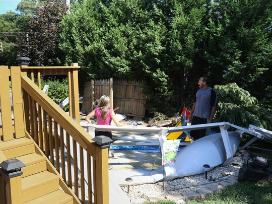 Charles Moulden and Tara Radcliff look out at the road from the back yard of their Belvedere home. On Sunday, a car careened through their fence and into the pool.