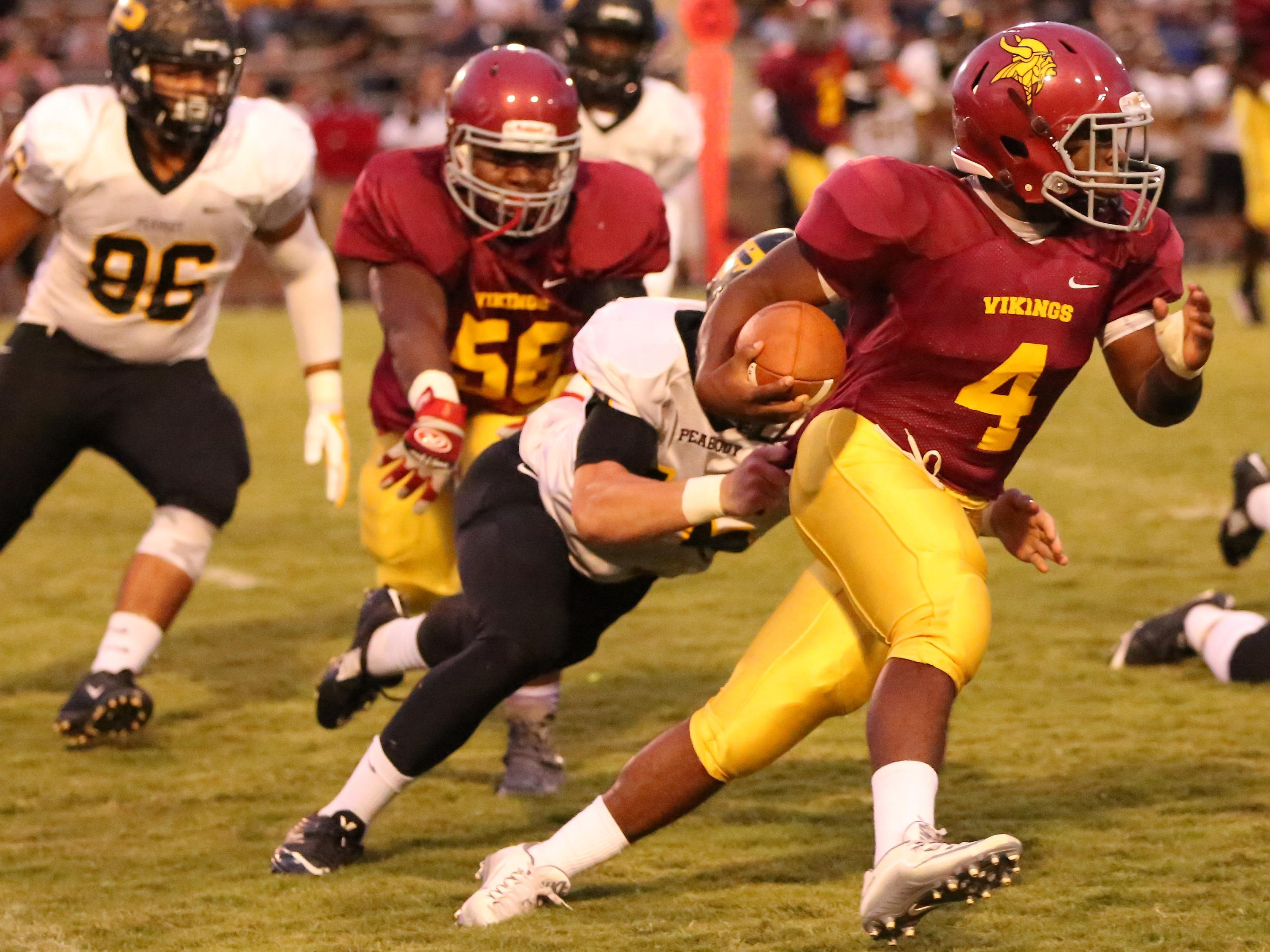 Humboldt's Jaylen Stewart runs around the end and shakes a Peabody tackle Friday night.