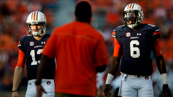 Auburn quarterback Sean White (13) and Auburn quarterback Jeremy Johnson (6) warm up before the NCAA football game between Auburn and Mississippi State on Saturday, Sept. 26, 2015, in Auburn, Ala.