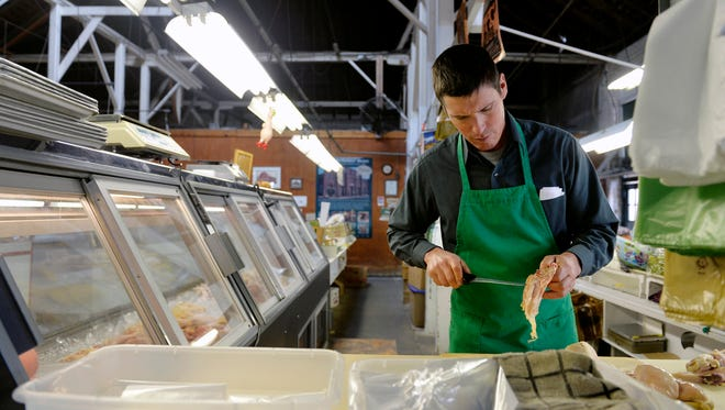 Andrew Miller, owner of the William L. Miller produce and poultry stand, cuts chicken breast fillets Friday at Market & Penn Farmers' Market in York. The market is changing its name to Penn Market as part of a wider marketing effort.