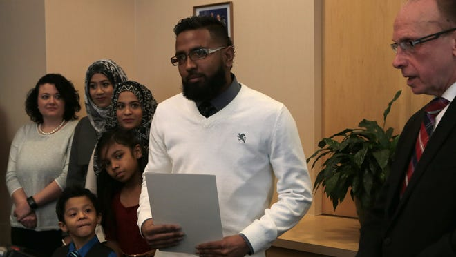 Didarul Sarder, 32, of Warren is humbled as he was honored by Warren Mayor Jim Fouts, as his family and co-worker watch to his left at the Warren City Hall on Thursday, Feb. 18, 2016.