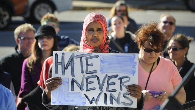 People hold signs during an anti-racism rally and march in Oct., 2014, at the Stearns County Courthouse in St. Cloud.